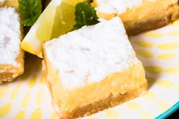 Keto Lemon bars on a plate with a sliced lemon and mint leaves