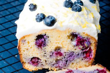a whole loaf of low carb blueberry bread topped with cream cheese frosting and blueberries on a black background