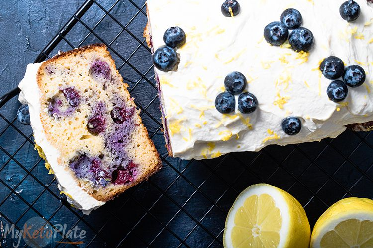 keto blueberry bread and slice on a black background and lemon